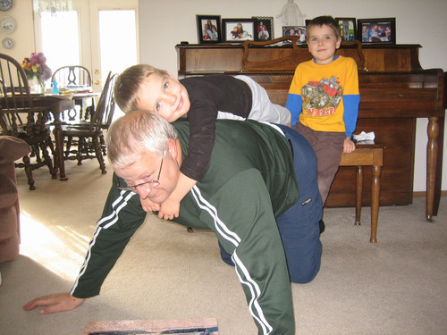 Braden Powell rides on the back of Chuck Cox, as Charlie Powell watches from the piano, in the living room of the Cox home in Puyallup, Wash. Photo courtesy of the Cox family