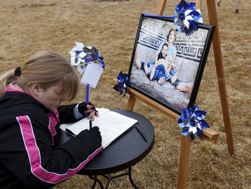 Trent Nelson  |  The Salt Lake Tribune Wendy Morgan writes her thoughts in a book at a community pinwheel vigil for Charlie and Braden Powell in the Municipal Gardens Playground Thursday in Ogden. The event was put on by Prevent Child Abuse Utah.