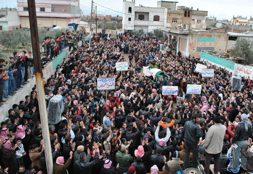 In this Tuesday, Feb. 7, 2012 photo, Syrian mourners carry the coffin, center, of a man who witnesses say was killed by Syrian government forces shelling, during a funeral procession in the Rastan neighborhood in Homs province, central Syria. The Arabic placards held by the mourners from right to left read: