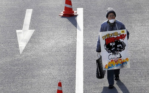 A protester carries a sign reading