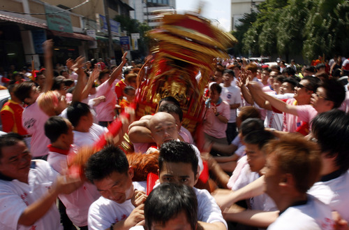 Malaysian Chinese devotees shake a deity statue while leaving the Johor Bahru Old Chinese Temple during an annual Chingay parade in Johor Bahru, southern Malaysia, Saturday, Feb. 11, 2012. Many festival goers turn out in the city to watch the religious procession which goes on for five days. (AP Photo/Lai Seng Sin)