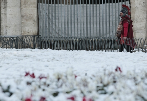 A man wearing a Roman centurion costume walks past Rome's Colosseum, Saturday, Feb. 11, 2012.  After about 26-years without large amounts of snowfall in Rome, the capital has been hit by its second snowstorm in a week.  Snow blanketed Rome's suburbs Friday morning, and by evening, it started sticking in the capital's center, and within two hours, at least 5 cm (2 inches) had accumulated. (AP Photo/Gregorio Borgia)
