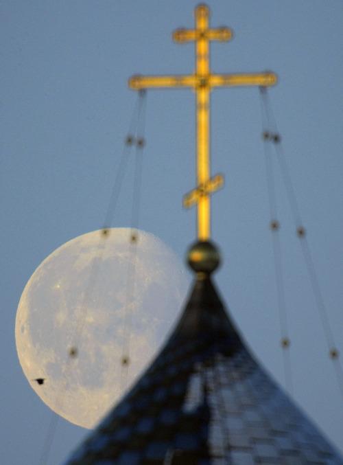 The nearly full moon sets behind an Orthodox church in Minsk, Belarus, Saturday, Feb. 11, 2012. (AP Photo/Sergei Grits)