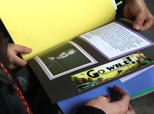 Rick Egan  | The Salt Lake Tribune  Funeralgoers thumb through a scrapbook with pictures of Charlie Powell, put together by his teacher, John Huson, before the funeral for Charlie and Braden Powell at the Life Center Church in Tacoma, Wash., on Saturday.