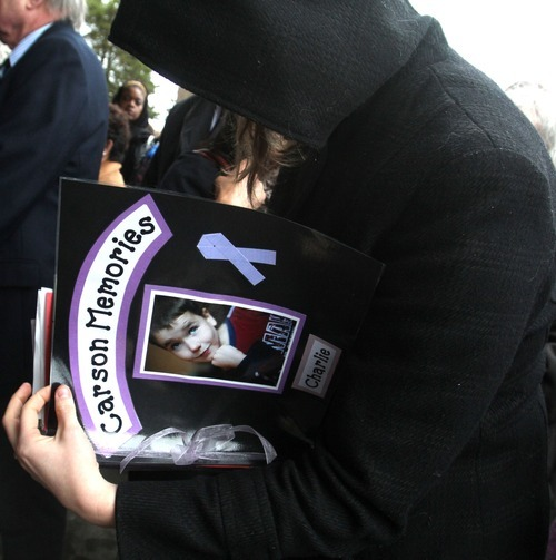Rick Egan  | The Salt Lake Tribune  Lonnie Hathaway, sister of Charlie's teacher, John Huson, looks through a scrapbook with pictures of Charlie Powell, put together by Huson, before the funeral for Charlie and Braden Powell at the Life Center Church in Tacoma, Wash., on Saturday.