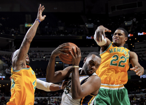 Utah Jazz center Al Jefferson, center, drives to the basket between Memphis Grizzlies forward Quincy Pondexter, left, and forward Rudy Gay (22) in the first half of an NBA basketball game on Sunday, Feb. 12, 2012, in Memphis, Tenn. (AP Photo/Nikki Boertman)