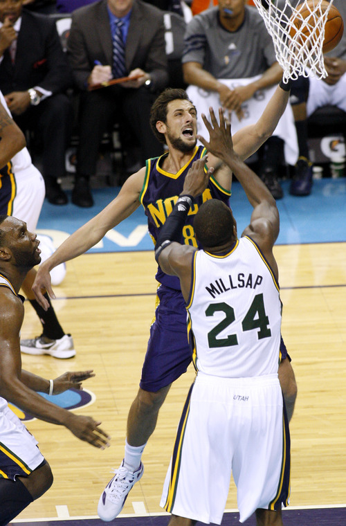 New Orleans Hornets shooting guard Marco Belinelli (8) shoots the ball over Utah Jazz power forward Paul Millsap (24) in the first half of an NBA basketball game in New Orleans, Monday, Feb. 13, 2012. (AP Photo/Jonathan Bachman)