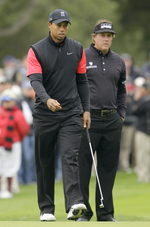 Tiger Woods, left, and Phil Mickelson walk on the first green at Pebble Beach Golf Links during the final round of the AT&T Pebble Beach National Pro-Am golf tournament in Pebble Beach, Calif., Sunday, Feb. 12, 2012. (AP Photo/Eric Risberg)