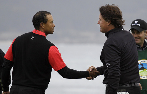 Tiger Woods, left, shakes hands with Phil MIckelson on the 18th green at Pebble Beach Golf Links during the final round of the AT&T Pebble Beach National Pro-Am golf tournament in Pebble Beach, Calif., Sunday, Feb. 12, 2012. Mickelson finished with an 8-under 64 to win the Pebble Beach National Pro-Am and become only the ninth player with 40 career PGA Tour wins. (AP Photo/Eric Risberg)