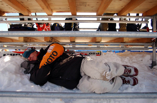 Francisco Kjolseth | Tribune file photo Photographer Tom Moran catches up on some sleep under the bleachers while waiting out a weather delay at the women's downhill at Snowbasin.