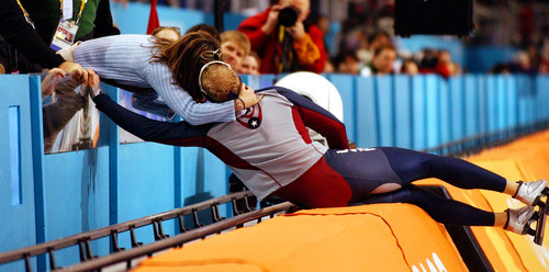 Danny La | Tribune file photo Speedskater Casey Fitzrandolph leans over the crash pads at the Utah Olympic Oval to embrace fiancee Jennifer Bocher after winning the men's 500 meters.