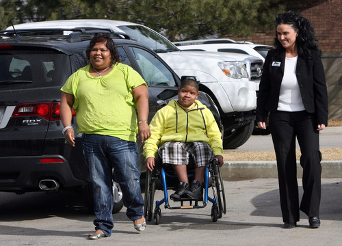 Steve Griffin  |  The Salt Lake Tribune  Beatriz Peralta, and her son Edwin Lopez Peralta, 13, get their first look at there new car at the Central Collision Center in Draper, Utah  Tuesday, February 14, 2012.  Bear River Mutual Insurance Co., Central Collision Center and several other local companies have combined resources to provide the single mother with a newly refurbished automobile.