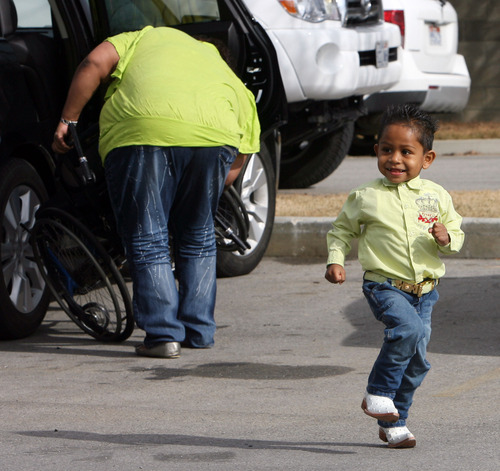 Steve Griffin  |  The Salt Lake Tribune  Angel Lopez Peralta, 3, runs around the parking lot at the Central Collision Center in Sandy, as his mother, Beatriz Peralta, back, helps is brother, Edwin Lopez Peralta, 13, out of the car in Draper, Utah  Tuesday, February 14, 2012.  Bear River Mutual Insurance Co., Central Collision Center and several other local companies have combined resources to provide single mother Beatriz Peralta with a newly refurbished automobile.