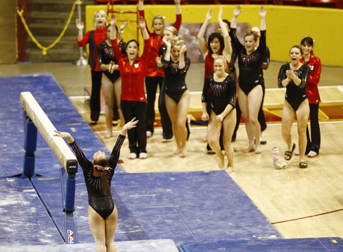 Photo by Rob Schumacher Utah's Corrie Lothrop dismounts from the beam as her teammates celebrates during Sunday's meet against PAC-12 foe Arizona State at Wells-Fargo Arena in Tempe.