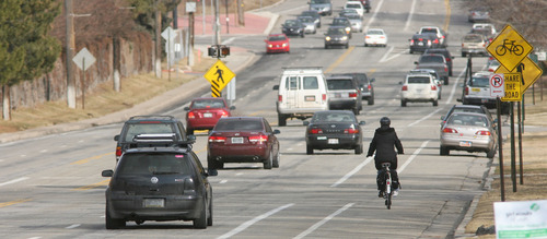 Steve Griffin  |  The Salt Lake Tribune A biker rides on the sidewalk on Sunnyside Avenue in Salt Lake City Wednesday.  Salt Lake City has delayed plans for a