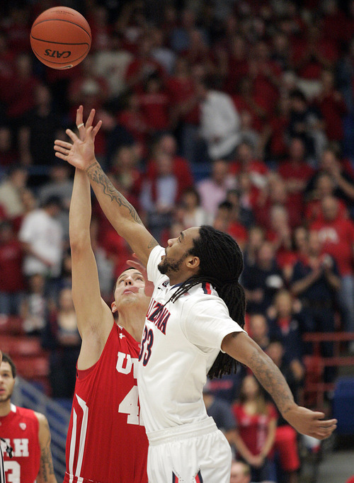 Arizona's Jesse Perry, right, and Utah's Jason Washburn (42) jump for the tip-off during the first half of an NCAA college basketball game at McKale Center in Tucson, Ariz., Saturday, Feb. 11, 2012. (AP Photo/Wily Low)