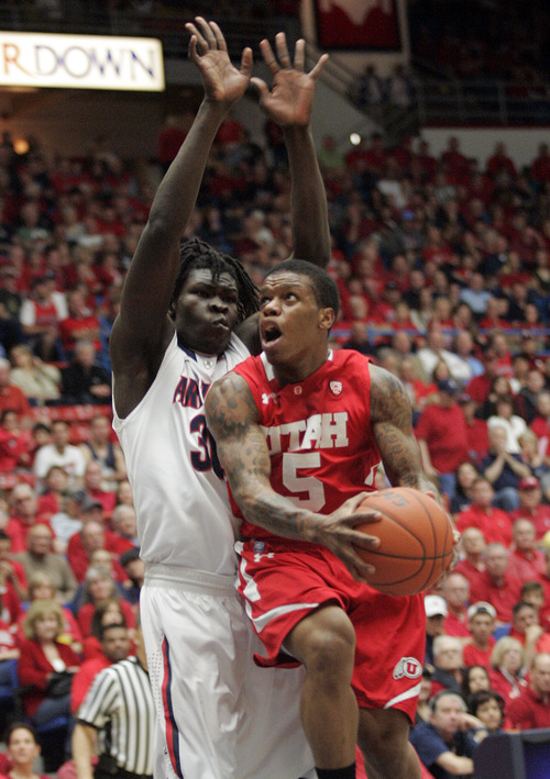 Utah's Kareem Storey (5) drives to the basket around Arizona's Angelo Chol (30) during the first half of an NCAA college basketball game at McKale Center in Tucson, Ariz., Saturday, Feb. 11, 2012. (AP Photo/Wily Low)