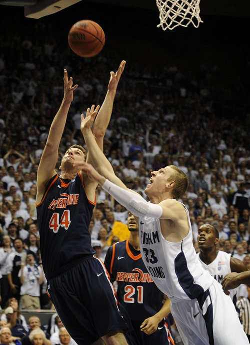 Pepperdine's Corbin Moore (44) and BYU's Nate Austin (33) fight for a rebound during the first half of an NCAA college basketball game at the Marriott Center in Provo, Utah, Saturday, Feb. 11, 2012. (AP Photo/The Daily Herald, James Roh)  MANDATORY CREDIT JAMES ROH/Daily Herald MANDATORY CREDIT