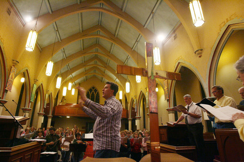 Steve Griffin  |  The Salt Lake Tribune  Conductor Brady Allred leads the Salt Lake Choral Artists as they perform the Bluegrass Mass during rehearsal at the First Baptist Church sanctuary.