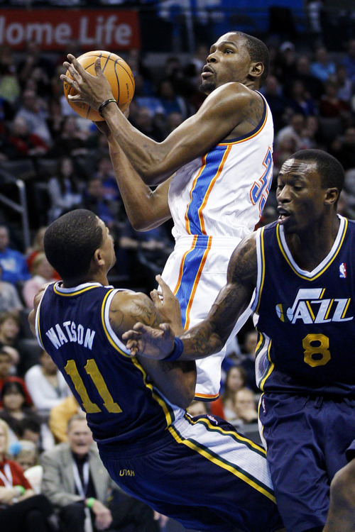Oklahoma City Thunder forward Kevin Durant, center, collides with Utah Jazz guard Earl Watson (11) as he goes up for a shot past Jazz forward Josh Howard (8) in the first quarter of an NBA basketball game in Oklahoma City, Tuesday, Feb. 14, 2012. (AP Photo/Sue Ogrocki)