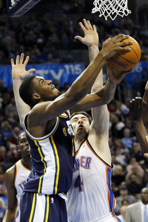 Utah Jazz forward Derrick Favors, left, shoots in front of Oklahoma City Thunder center Nick Collison, right, in the third quarter of an NBA basketball game in Oklahoma City, Tuesday, Feb. 14, 2012. Oklahoma City won 111-85. (AP Photo/Sue Ogrocki)
