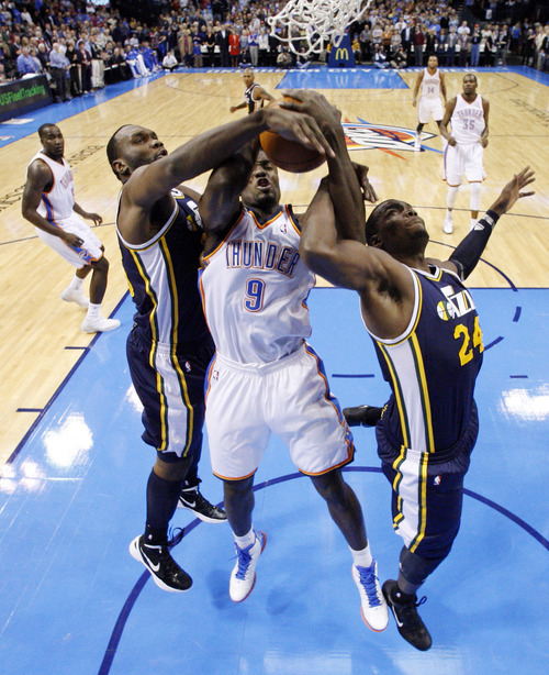 Utah Jazz center Al Jefferson, left, Oklahoma City Thunder forward Serge Ibaka (9), of Republic of Congo, and Jazz forward Paul Millsap (24) fight for a rebound in the first quarter of an NBA basketball game in Oklahoma City, Tuesday, Feb. 14, 2012. Oklahoma City won 111-85. (AP Photo/Sue Ogrocki)