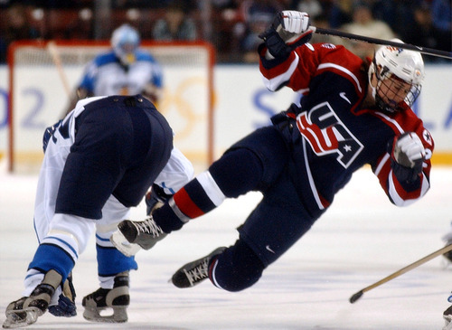 Danny La | Tribune file photo Tara Mounsey of the United States goes airborne after colliding with Finland's Katja Riipi during a 5-0 American victory in a preliminary-round women's hockey game at the E Center in West Valley City.
