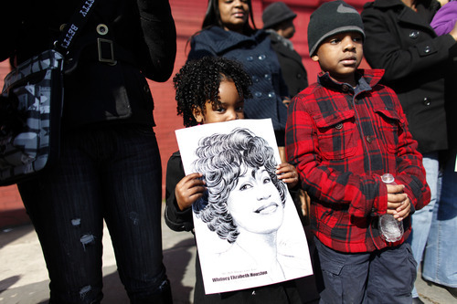 Kazarah Campbell, 4, of Newark, N.J., holds a sign as she and other Whitney Houston fans gather a few blocks from the New Hope Baptist Church before the singer's funeral in Newark, N.J., Saturday, Feb. 18, 2012. Houston died last Saturday at the Beverly Hills Hilton in Beverly Hills, Calif., at the age 48. (AP Photo/Jason DeCrow)