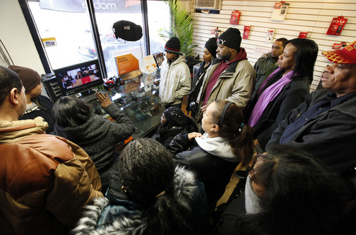 Whitney Houston fans gather around a television in a mobile phone store a few blocks from the New Hope Baptist Church to watch the singer's funeral in Newark, N.J., Saturday, Feb. 18, 2012. Houston died last Saturday at the Beverly Hills Hilton in Beverly Hills, Calif., at the age 48. (AP Photo/Jason DeCrow)