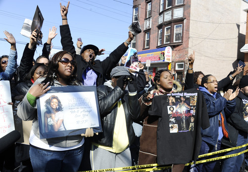 Fans sing near the funeral service for singer Whitney Houston at the New Hope Baptist Church in Newark, N.J., Saturday, Feb. 18, 2012. (AP Photo/Charles Sykes)