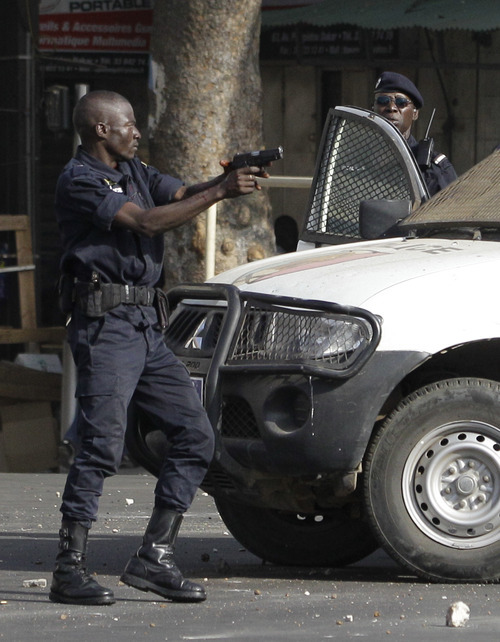 A policeman reacts by firing live rounds from a pistol, after being struck in the head with a rock by anti-government protesters, during running clashes in central Dakar, Senegal Friday, Feb. 17, 2012. Anti-government protesters and police clashed for a third consecutive day Friday, engaging in running street battles of rock throwing and tear gas in the streets of Dakar's downtown Plateau neighborhood. Demonstrators are defying a government ban on protests to call for the departure of 85-year-old President Abdoulaye Wade, who is running for a third term in next week's election.(AP Photo/Rebecca Blackwell)