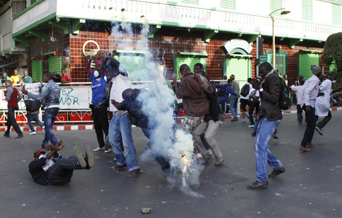 A tear gas canister explodes amidst a small group of protesters chanting slogans in central Dakar, Senegal Friday, Feb. 17, 2012. Anti-government protesters and police clashed for a third consecutive day Friday, engaging in running street battles of rock throwing and tear gas in the streets of Dakar's downtown Plateau neighborhood. Demonstrators are defying a government ban on protests to call for the departure of 85-year-old President Abdoulaye Wade, who is running for a third term in next week's election.(AP Photo/Rebecca Blackwell)