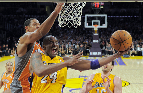 Los Angeles Lakers guard Kobe Bryant, right, puts up a shot as Phoenix Suns center Channing Frye during the second half of their NBA basketball game, Friday, Feb. 17, 2012, in Los Angeles. The Lakers won 111-99. (AP Photo/Mark J. Terrill)