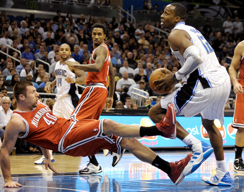 Milwaukee Bucks forward Jon Brockman (40) falls backwards after colliding with Orlando Magic center Dwight Howard, right, during the second half of an NBA basketball game in Orlando, Fla., Friday, Feb. 17, 2012. Bucks' Brandon Jennings, center, and Magic's Jameer Nelson (14) watch the play. The Magic won 94-85. (AP Photo/Phelan M. Ebenhack)