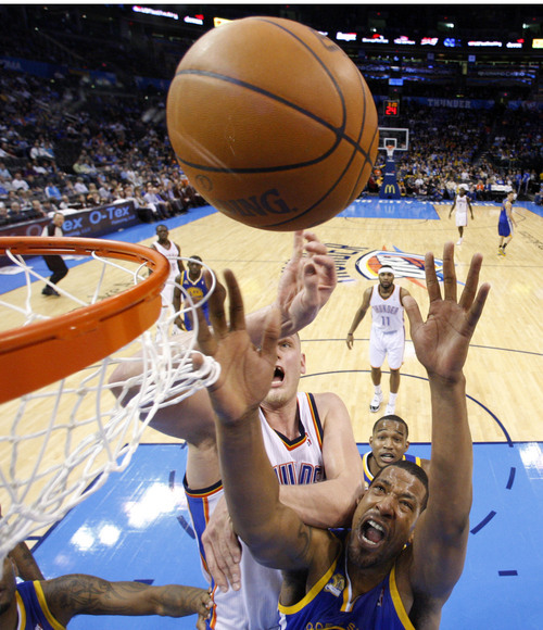 Golden State Warriors forward Dominic McGuire, bottom, rebounds in front of Oklahoma City Thunder center Cole Aldrich, rear, in the fourth quarter of an NBA basketball game in Oklahoma City, Friday, Feb. 17, 2012. Oklahoma City won 110-87. (AP Photo/Sue Ogrocki)