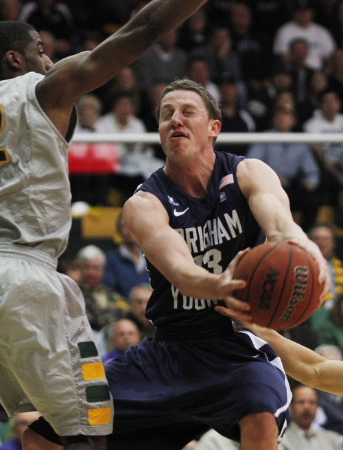 BYU's Brock Zylstra, right, shoots as San Francisco's Avery Johnson defends during the first half of an NCAA college basketball game in San Francisco, Thursday, Feb. 16, 2012. (AP Photo/George Nikitin)
