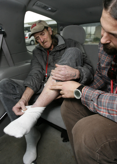 Al Hartmann  |  The Salt Lake Tribune Joel Hunt, a physician assistant for the Fourth Street Clinic, right, confers with Jeffrey Moss about wounds on his legs as they drive to Moss' methadone appointment. Hunt is part of a mobile medical team that is keeping the city's uninsured and homeless from cycling through hospital ER's.