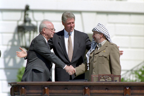 Israeli Prime Minister Yitzhak Rabin and Chairman of the Palenstinian Liberation Organization Yasser Arafat shake hands with President Clinton behind them at the Middle East Peace Agreement Ceremony on the South Lawn at the White House. (September 13, 1993) Credit: Courtesy of William J. Clinton Presidential Library