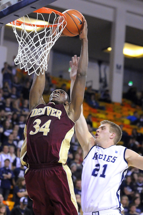 Denver forward Chris Udofia (34) dunks as Utah State forward Morgan Grim defends during an NCAA college basketball game Wednesday, Nov. 30, 2011, in Logan, Utah. (AP Photo/The Herald Journal, Eli Lucero)