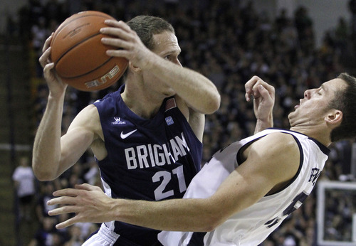 BYU forward Stephen Rogers (21) tries to get around Utah State forward Mitch Bruneel (15) during the first half of an NCAA college basketball game, Friday, Nov. 11, 2011, in Logan, Utah. (AP Photo/Jim Urquhart)