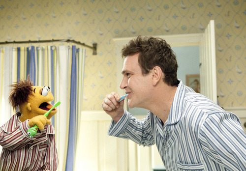 In this film publicity image released by Disney, muppet character Walter, left, and Jason Segel are shown with the muppet characters in a scene from