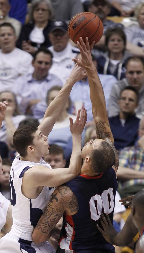 Gonzaga's Robert Sacre, right, blocks the shot of BYU's Matt Carlino during the first half of an NCAA college basketball game in Provo, Utah, Thursday, Feb. 2, 2012. (AP Photo/George Frey)