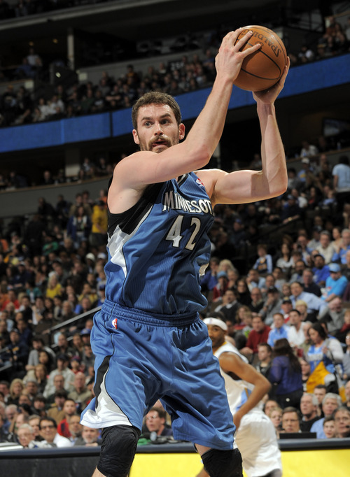 Minnesota Timberwolves forward Kevin Love (42) pulls down a rebound against the Denver Nuggets during an NBA basketball game on Monday, Feb. 20, 2012, in Denver. Denver beat Minnesota 103-101 in overtime. (AP Photo/Jack Dempsey)