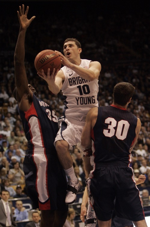 Kim Raff |The Salt Lake Tribune BYU player Matt Carlino goes for a layup as Gonzaga players (left) Sam Dower and (right) Michael Hart defend during the second half at the Marriott Center in Provo, Utah on February 2, 2012.  BYU went on to win the game 83-73.