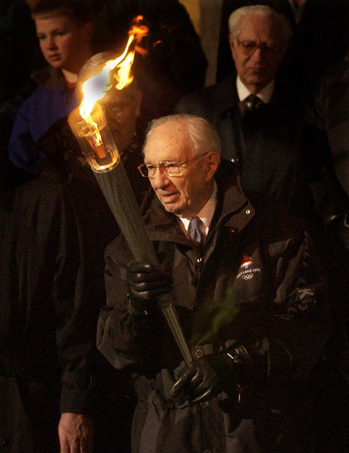 Tribune file photo LDS Church President Gordon B. Hinckley holds the Olympic torch before passing it on to apostle Neal A. Maxwell, at the Church Administration Building, at the start of the 2002 Salt Lake Olympics.