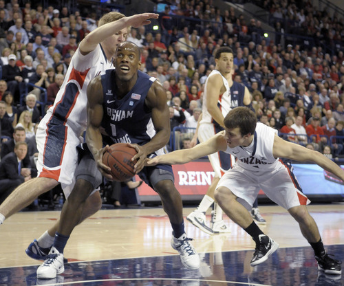 Bringman Young's Charles Abouo is defended by Gonzaga's Kevin Pangos, right, and Mathis Moeninghoff in the first half of an NCAA college basketball game, Thursday, Feb. 23, 2012, in Spokane, Wash. (AP Photo/Jed Conklin)