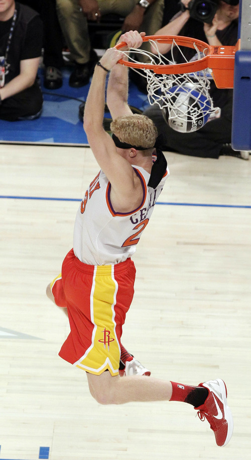 Houston Rockets' Chase Budinger finishes a blindfolded dunk in honor of former Phoenix Suns' Cedric Ceballos, who performed a blindfolded dunk in 1992, during the NBA basketball All-Star Slam Dunk contest, Saturday, Feb. 25, 2012, in Orlando, Fla. (AP Photo/Chris O'Meara)