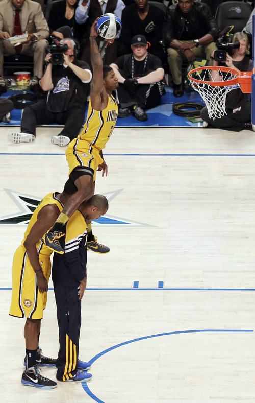 Indiana Pacers' Paul George jumps over two teammates on his attempt during the NBA basketball All-Star Slam Dunk Contest in Orlando, Fla., Saturday, Feb. 25, 2012. (AP Photo/Chris O'Meara)
