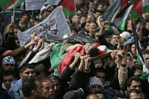 Palestinians carry the body of Talat Ramia during his funeral in the West Bank town of Al-Ram, near Jerusalem, Saturday, Feb. 25, 2012.  On Friday Ramia was shot dead by Israeli forces while throwing fire crackers at them. The army said it is investigating the shooting. (AP photo/Majdi Mohammed)