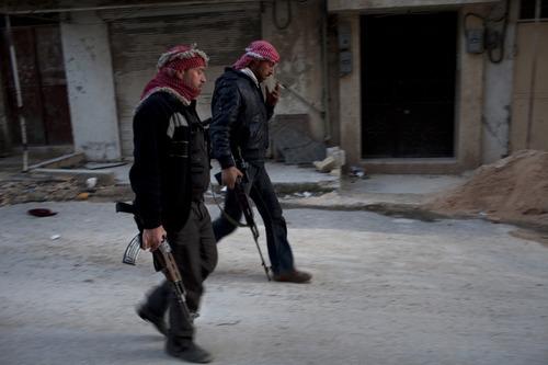 Free Syrian Army fighters walk towards a check point near their headquarters in Kafar Taharim, north Syria, Friday, Feb. 24, 2012. (AP Photo/Rodrigo Abd)